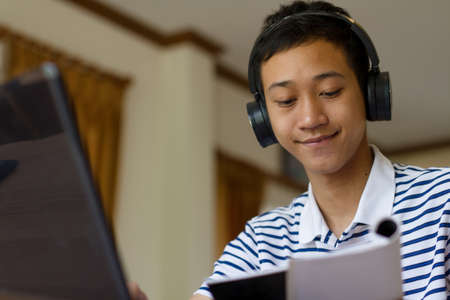 Happy young asian man wear headphone and smilling is learning an english language from online teacher by video call or webinar at home. online class, video conference or meeting due distance.