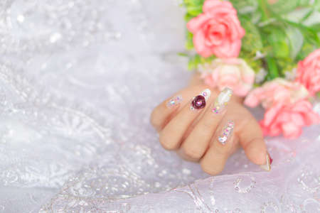 woman acrylic fingernail painting beautiful white color gel nail art decorated with cute 3D rose flower sparkling rhinestone sweet and luxury design for valentine day 写真素材