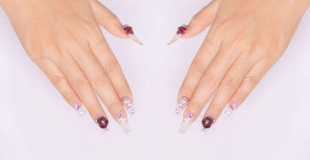 woman acrylic fingernail painting beautiful white color gel nail art decorated with cute 3D rose flower sparkling rhinestone sweet and luxury design for valentine day