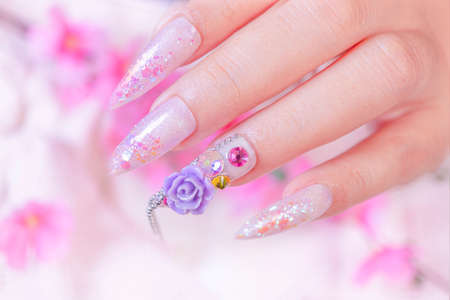 close up luxury woman hand manicure with acrylic extension stiletto style painting sweet ombre pink glitter decorated with beautiful light purple rose and sparkling rhinesotne