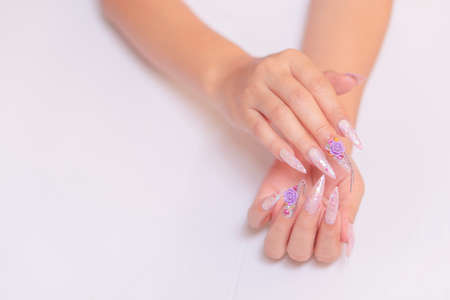 trendy woman hand manicure with long acrylic extension stiletto style painting sweet ombre pink glitter decorated with beautiful light purple rose and sparkling rhinesotne with copy space 写真素材