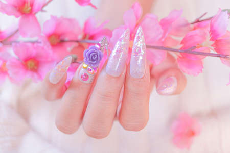 close up woman hand manicure with long acrylic extension stiletto style painting sweet ombre pink glitter decorated with beautiful light purple rose and sparkling rhinesotne