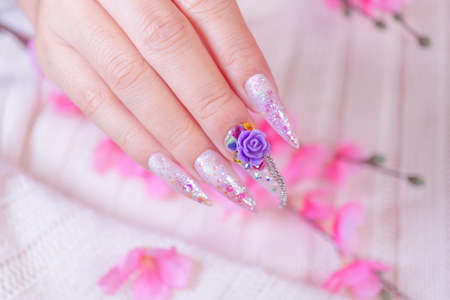 close up glamorous woman hand manicure with long acrylic extension stiletto style painting sweet ombre pink glitter decorated with beautiful light purple rose and sparkling rhinesotne 写真素材