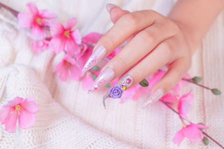 luxury woman hand manicure with long acrylic extension stiletto style painting sweet ombre pink glitter decorated with beautiful light purple rose flower and sparkling rhinesotne 写真素材