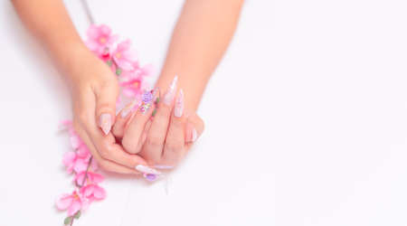 attractive woman hand manicure with long acrylic extension stiletto style painting sweet ombre pink glitter decorated with beautiful light purple rose and sparkling rhinesotne with copy space