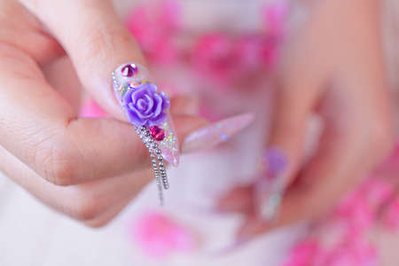 close up glamorous woman hand manicure with long acrylic extension stiletto style painting sweet ombre pink glitter decorated with beautiful light purple rose and sparkling rhinesotne on thrumbnail