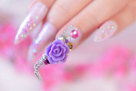 close up woman hand manicure with long acrylic extension stiletto style painting sweet ombre pink glitter decorated with beautiful light purple rose and sparkling rhinesotne for valentime