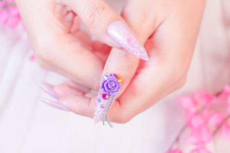 close up luxury woman hand manicure with long acrylic extension stiletto style painting sweet ombre pink glitter decorated with beautiful light purple rose and sparkling rhinesotne on thrumbnail 写真素材