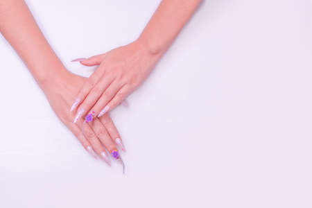 woman hand manicure with long acrylic extension stiletto style painting sweet ombre pink glitter decorated with beautiful light purple rose and sparkling rhinesotne