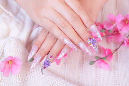 woman hand manicure with long acrylic extension stiletto style painting sweet ombre pink glitter decorated with beautiful light purple rose flower and sparkling rhinesotne