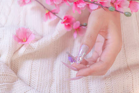 woman hand manicure with long acrylic extension stiletto style painting sweet ombre light pink glitter decorated with beautiful light purple rose and sparkling rhinesotne 写真素材