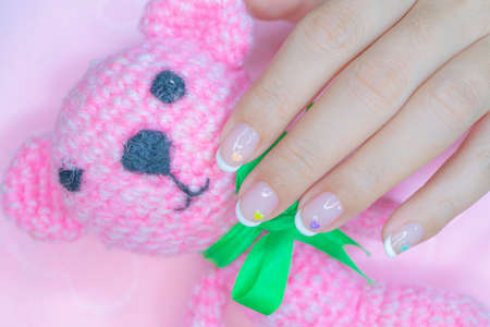 beautiful white french manicure on woman short fingernail decorated  with cute pastel litte heart 写真素材