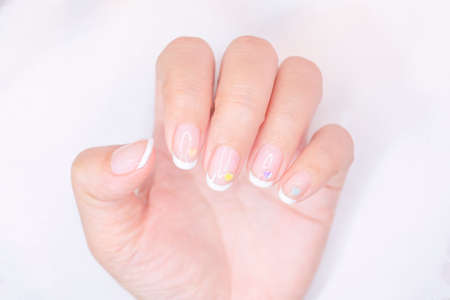sweet beautiful white french manicure on woman short fingernail decorated  with cute pastel litte heart on white background