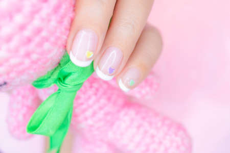 sweet beautiful white french manicure on woman short fingernail decorated  with cute pastel litte heart