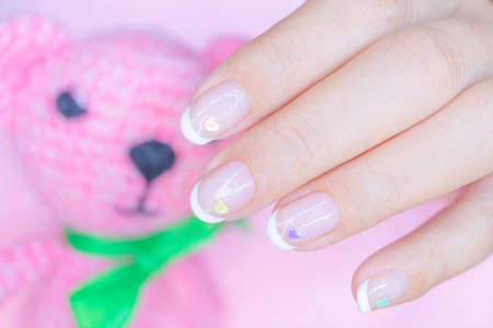 close up sweet beautiful white french manicure on woman short fingernail decorated  with cute pastel litte heart