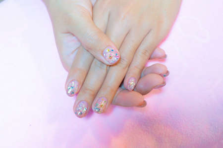 Beautiful sparkling silver glitter gel nail art decorated with real dry flower on fasionista woman short fingernail isolated on white background