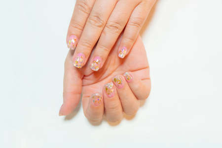 Beautiful Trendy crack shell decorated on woman short fingernail with sparkling silver and gold glitter in clear gel nail art isolated on white background 写真素材