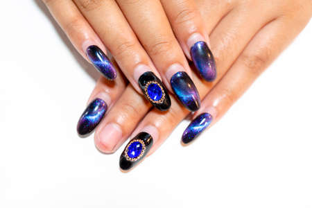 Close up Shiny dark blue magnetic design gel nail art painting on woman acrylic fingernail almond shape decorated with sparkling big diamond on ringfinger,hand manicure after painting one month