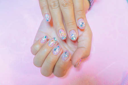 close up Beautiful sparkling silver glitter gel nail art decorated with real dry flower on fasionista woman short fingernail isolated on white background