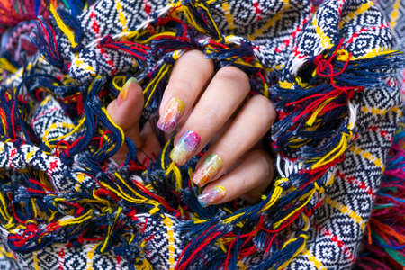 Colorful gel polish painting cute galaxy nail art on beautiful woman fingernail