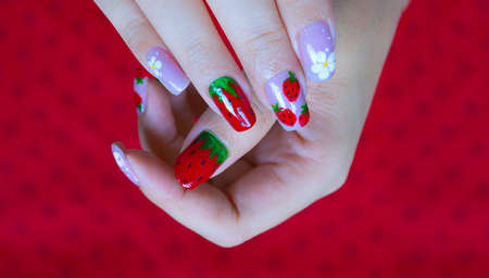 close up sweet shiny baby purple and dark red gel polish painting cute white little flower and strawberry  on woman short square shape fingernail