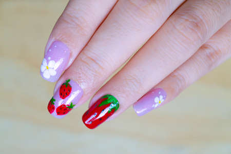 close up sweet shiny baby purple and dark red gel polish painting cute white little flower and yummy strawberry  on woman short square shape fingernail