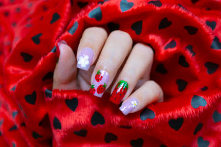 sweet shiny baby purple and red gel polish painting cute white little flower and yummy strawberry  on woman short square shape fingernail 写真素材