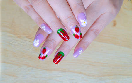 sweet shiny bright purple and dark red gel polish painting cute white little flower and yummy strawberry  on woman short square shape fingernail
