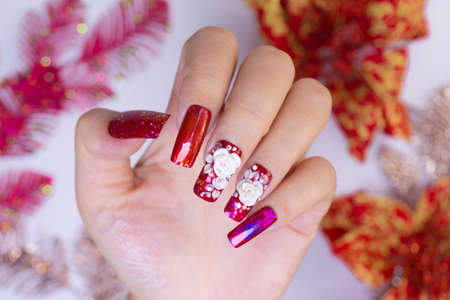 close up sparkling red color gel polish painting 3D rose flower decorate d with shiny rhinestone and glitter on fashionista woman long square shape acrylic fingernail