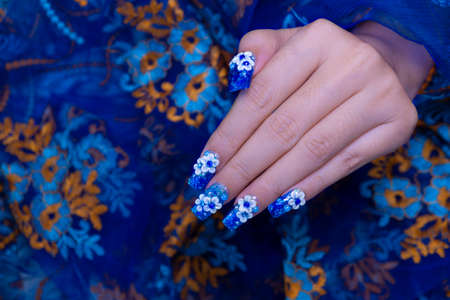 beautiful shiny dark blue glitter gel nail art ombre design painting 3D white cute flower decorated with rhinestone on woman long square shape fingernail