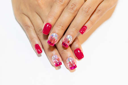 Close up Woman hand manicure painting dark pink gel polish decorated with silver pink glitter omber design isolated on White background