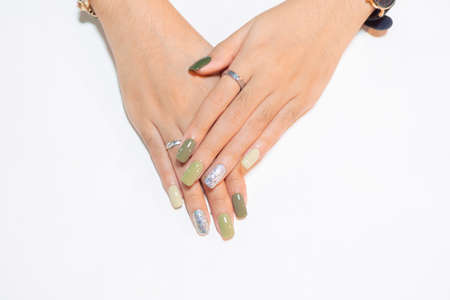 woman fingernail square shape painting beautiful shiny green color gel polish with sparking silver gliitter on ringfinger isolated on white background Reklamní fotografie