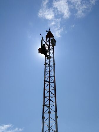 Silhouette worker maintenance wind direction sensor on tower, Meteorological.