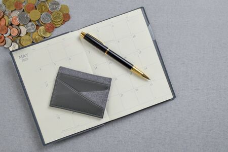 Black and gold fountain pen placed and pocket on blank planner book with pile of Thai Baht coin. Zdjęcie Seryjne