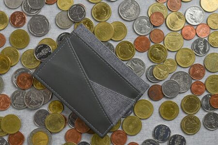 Pocket / card holder place on a pile of Thai Baht coins on gray cement texture background. Financial and expense concept.