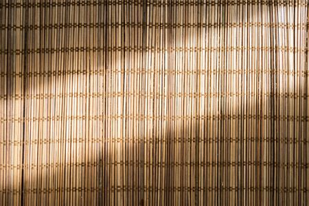 Brown bamboo mat, striped wicker in hard light. Natural wicker pattern for background.