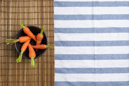Baby carrots arranged in a circle in black bowl like a hexagonal camera aperture diaphragm placed on brown bamboo mat over white table cloth with blue stripe. Flat lay, top view, creative layout with copy space.