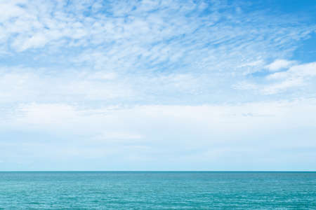 White clouds on blue sky over the calm ocean in sunny day at the Gulf of Thailand. Natural background of beautiful seascape.