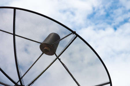 Close up black antenna communication satellite dish on cloudy sky background, network connection technology