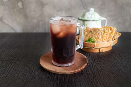Fresh Indonesian ice tea drink inside big mug glass in top of wood plate with dark wood background