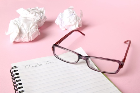 spiral book: Concept of writers block. Notebook with Chapter One written in it, with glasses and crumpled paper in the background.  Stock Photo