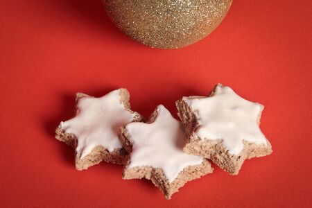 likeness: Three star-shaped Christmas biscuits, facing golden Christmas ball, on red background. Likeness with the three wise man following the star.