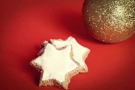 Two cinnamon stars and a golden Christmas ball on red background Stock Photo - 11355000