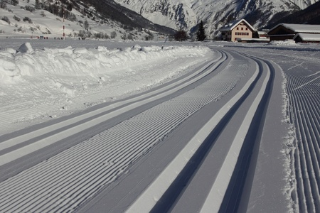 Freshly prepared track for nordic skiing, with sparkling snow and houses in the background. photo