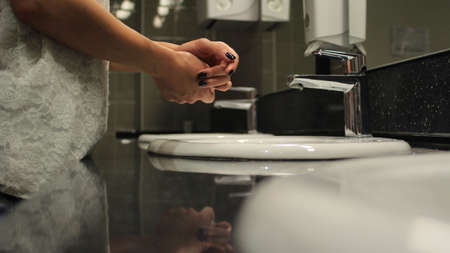 sink drain: female hands over the sink in a public restroom