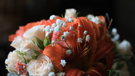 Cream roses,orange lilies and tiny white flowers,details of the wedding bouquet