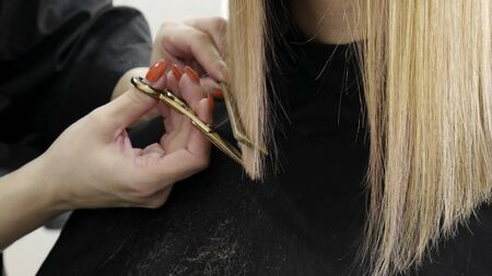 Close up of beauticians hand with a comb cutting hair of woman
