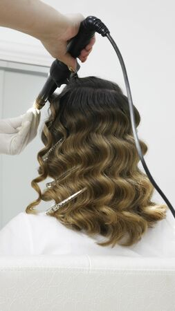 Professional hairdresser hands curling hair in the salon - view from behind