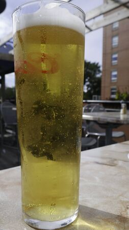 Glass of light beer on a outdoor table