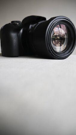 Black digital camera on a light background Фото со стока